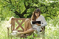 Young woman using digital tablet on wooden bench in a garden - LAF000889