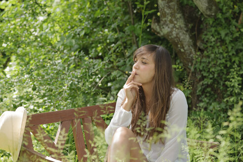 Young woman smoking on wooden bench in a garden - LAF000895