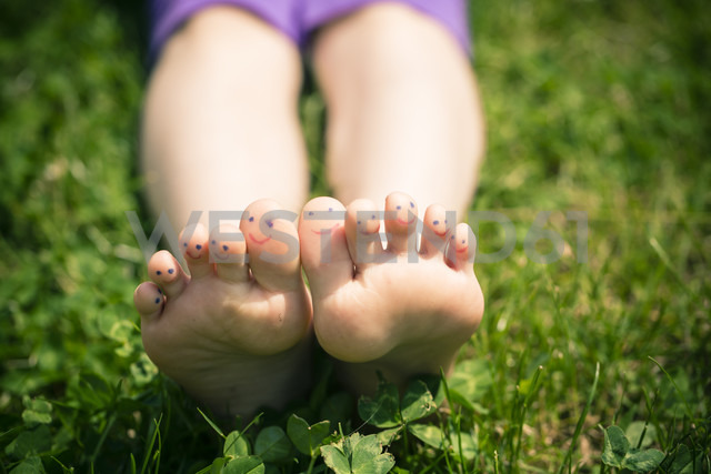 Little girl's feet with painted toes lying in grass - SARF000692