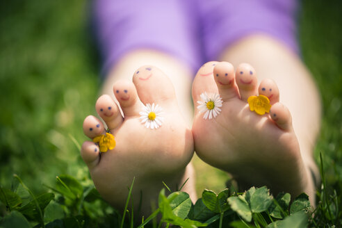 Little girl's painted toes decorated with daisies, Bellis perennis, and buttercups, Ranunculus - SARF000695