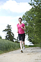 Female jogger running on field path - MAEF008380