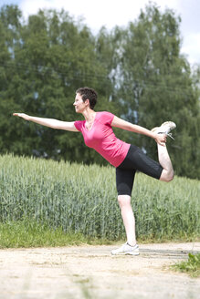 Woman making stretching exercises outside - MAEF008426