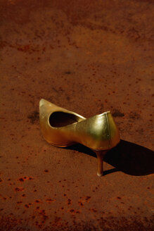Golden stiletto on a rusty table - AXF000694