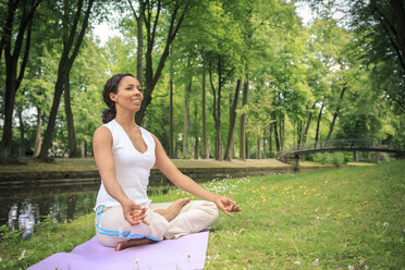 Germany, Woman exercising yoga in a park - VTF000276