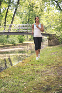 Geramny, Bavaria, Bayreuth, Woman jogging by a river in the city park - VTF000281
