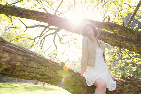 Smiling young woman sitting on a branch in a park at backlight - BMA000064