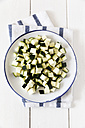Bowl of diced courgettes on kitchen towel and white wood, elevated view - EVGF000613