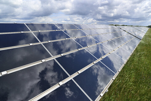 Germany, photoelectric cells of solar power plant with reflections of clouds, partial view - LY000059