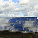 Germany, photoelectric cells of solar power plant with reflections of clouds, partial view - LYF000064
