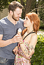 Portrait of happy young couple with ice-cream cone looking each other - FCF000235