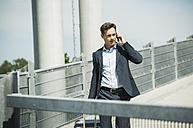 Business man with rolling suitcase telephoning with smartphone - UUF000883