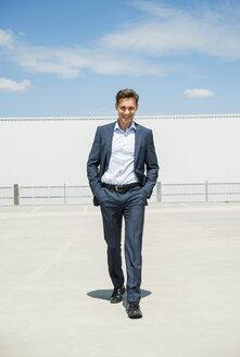 Smiling business man walking on parking level - UUF000915