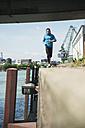 Man with headphones jogging at riverside - UUF000919