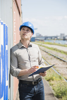 Portrait of man with blue safety helmet checking cargo containers - UUF000942