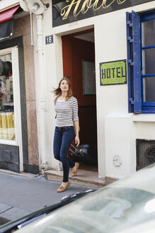 France, Paris, portrait of young woman with rolling suitcase leaving hotel - FMKF001245
