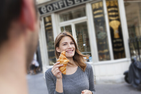 France, Paris, portrait of young woman showing croissant in front of pastry shop - FMKF001352