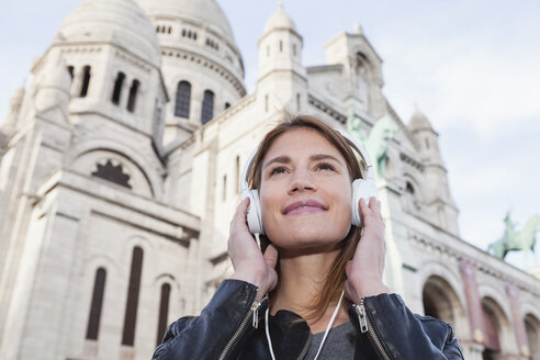 France, Paris, portrait of happy young woman listening music with headphones in front of Sacre Coeur - FMKF001261