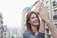 France, Paris, portrait of smiling young woman giving high five to her boyfriend - FMKF001270