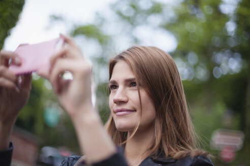 France, Paris, portrait of smiling young photographing with her smartphone - FMKF001273
