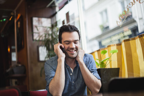 France, Paris, portrait of man telephoning with his smartphone in a cafe - FMKF001278