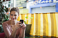 France, Paris, portrait of smiling young woman with her smartphone in a cafe - FMKF001281
