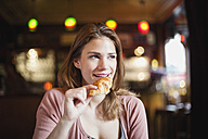 France, Paris, portrait of happy young woman eating a croissant in a cafe - FMKF001287