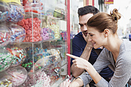 France, Paris, couple looking at sweets in a window display - FMKF001293