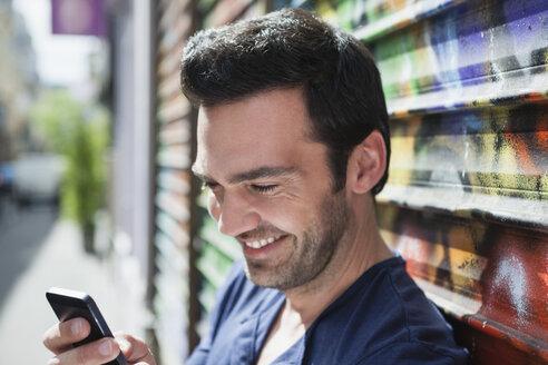France, Paris, portrait of smiling man using his smartphone - FMKF001296