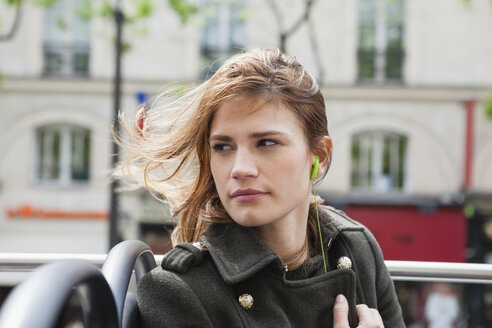 France, Paris, portrait of young woman sitting in a tour bus - FMKF001308