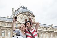 France, Paris, couple photographing  themself with smartphone - FMKF001330