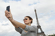 France, Paris, portrait of young woman photographing herself with tablet computer in front of Eiffel Tower - FMKF001333