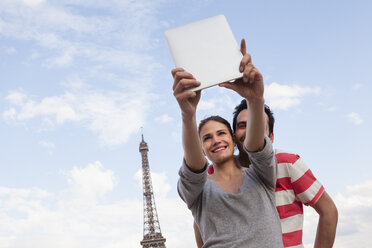 France, Paris, couple photographing  themself with tablet computer in front of Eiffel Tower - FMKF001336