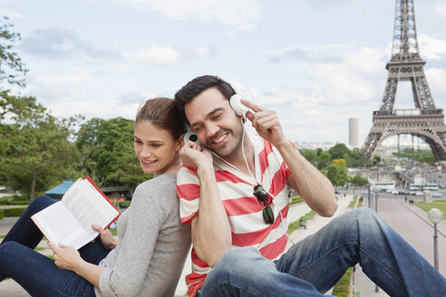 France, Paris, portrait of couple with travel guide and headphones in front of Eiffel Tower - FMKF001339