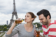 France, Paris, portrait of couple relaxing in front of Eiffel Tower - FMKF001341