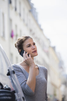 France, Paris, portrait of young telephoning with her smartphone - FMKF001319
