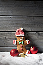 Gingerbread man and Christmas bubbles on artificial snow in front of grey wooden wall - CSF021675