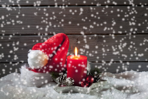 Lighted red candle and Christmas cap with rippling artificial snow in front - CSF021678