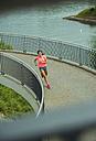 Young woman jogging on a bridge - UUF000949
