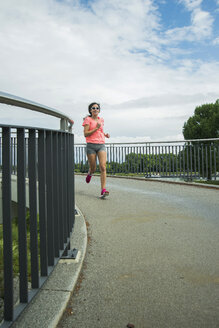 Young woman jogging on a bridge - UUF000953