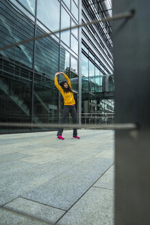 Young woman wearing yellow tracksuit top making stretching exercises - UUF000984