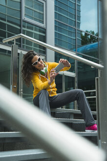 Young woman wearing yellow tracksuit top photographing herself with smartphone - UUF000990