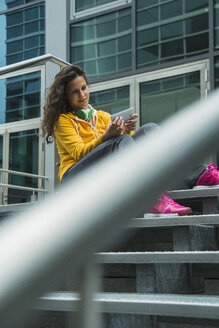 Young woman wearing yellow tracksuit top using smartphone - UUF000991