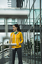 Young woman wearing yellow tracksuit top - UUF001009