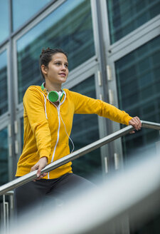 Portrait of young woman wearing yellow tracksuit top - UUF000999