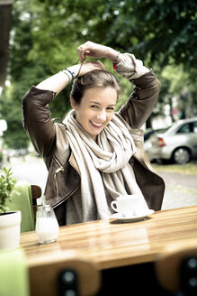 Portrait of smiling young woman sitting in street cafe - FX000022