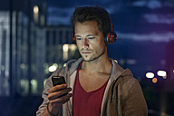 Portrait of young man with smartphone and earphones listening music at night - RBF001799
