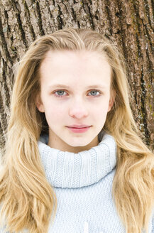 Portrait of pale female teenager wearing lightblue turtleneck standing in front of tree - FCF000249