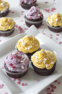 Plate of chocolate muffins with lemon curd decorated with baking dekor on white wood - YFF000176