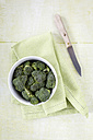 Bowl of broccoli florets, kitchen knife and cloth on wood - EVGF000690