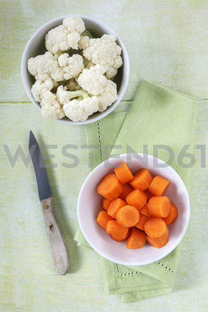 Bowls of cauliflower florets and sliced carrots, kitchen knife and cloth on wood - EVGF000693